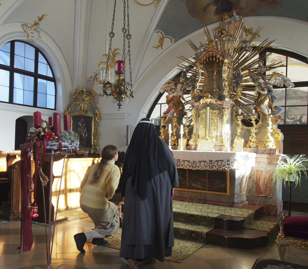 Sister Apollonia Buchinger, right, and postulant Claudia Schwarz kneel at the altar in the abbey in Altomuenster, Germany, on Dec. 6. The library holds in excess of 500 books that were off limits to all but the abbey's nuns for over five centuries.
