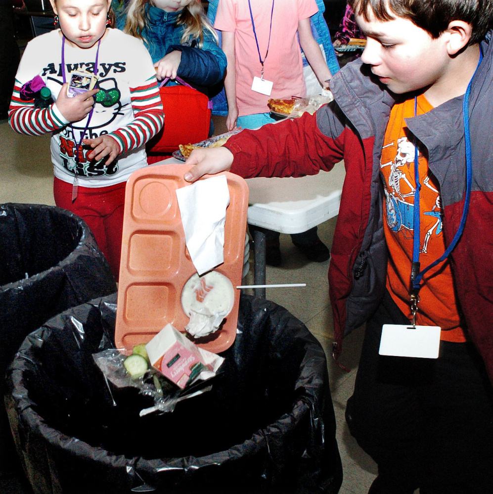 Winslow Elementary School student Aidan Giguere and other students empty food waste into trash cans in the school cafeteria on Dec. 22. Winslow is looking at a food waste recycling program for the school. David Leaming/Morning Sentinel