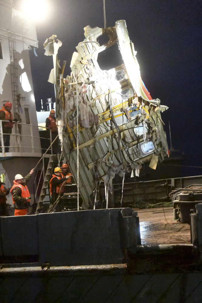Russian Emergency Ministry employees lift a fragment of a plane outside Sochi, Russia. Rescue workers on Tuesday found a flight recorder from the Russian plane that crashed into the Black Sea over the weekend, the defense ministry said. All 84 passengers and eight crew members on the Russian military's Tu-154 plane are believed to have died.