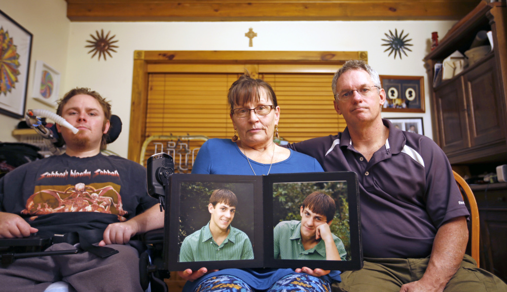 "The Norton family is mourning ""JT"" Norton, who had schizophrenia. From left are brother Michael, mother Suzan – holding a photo of JT when he was younger – and father Terrence."