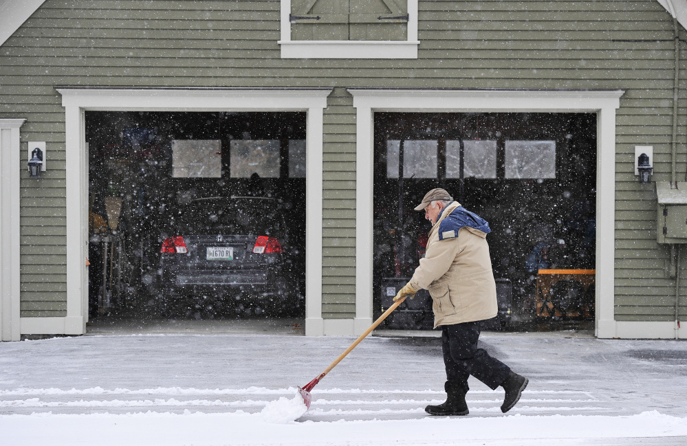 Wayne Hutchins 78, of Dayton scrapes a layer of light snow from his driveway Thursday afternoon. The storm is expected to end by Friday morning, with skies gradually clearing throughout the day.