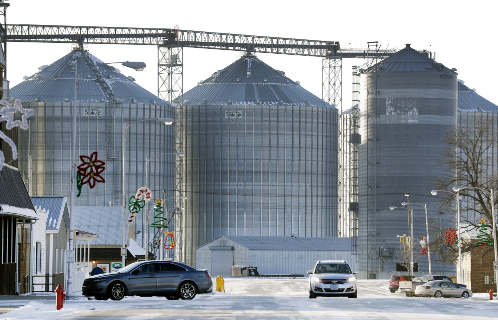 A motoristr passes the grain elevator this month in Renwick, Iowa. When the once-bustling town's sole bar closed this year, a group of friends pooled their money to repair and reopen the place as the Blue Moose Saloon.