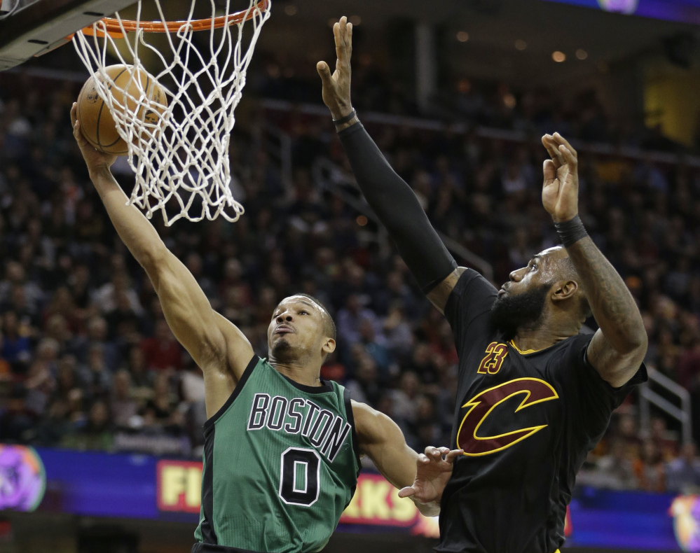 Boston's Avery Bradley drives to the basket against LeBron James in the first half Thursday in Cleveland.