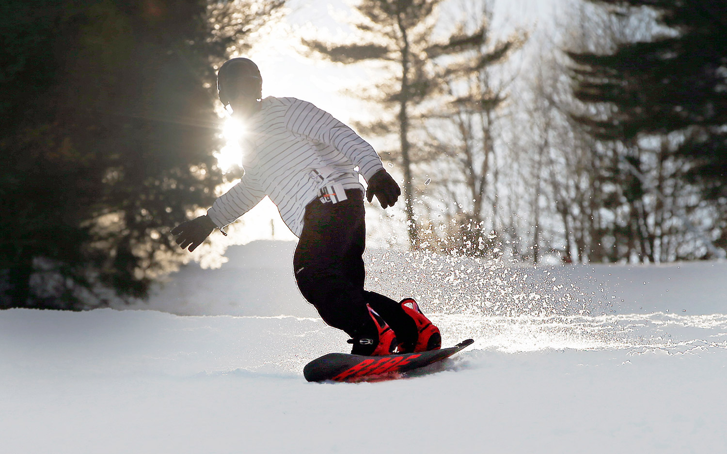A snowboarder takes a run at Shawnee Peak in Bridgton on Tuesday. Ski resort managers are cautiously optimistic that snowfall totals will beat last winter's. Ben McCanna/Staff Photographer