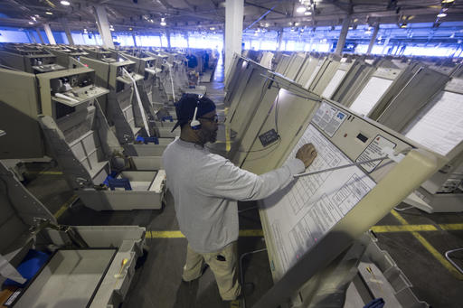 A technician prepares a voting machine for use before November's U.S. election.