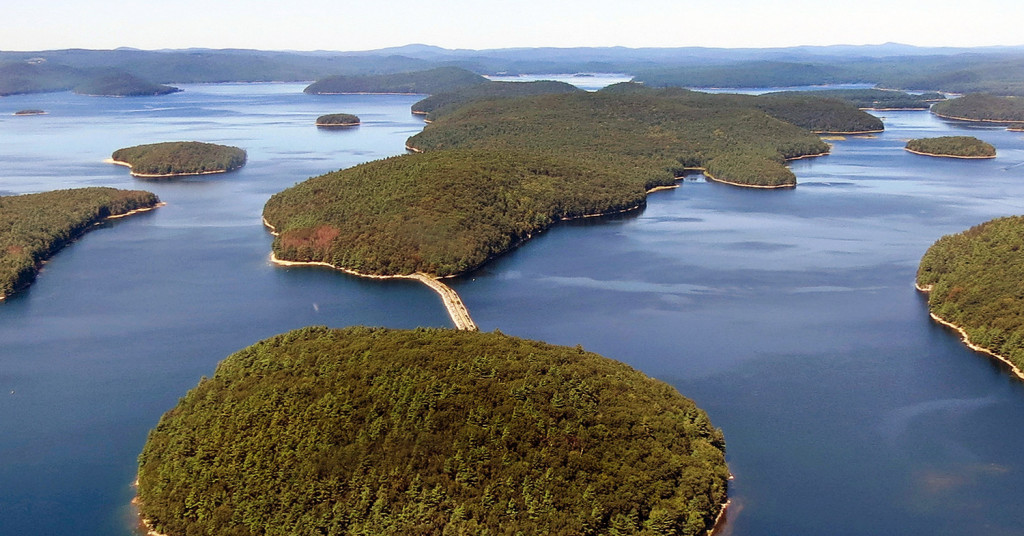 A dirt and stone road leads to Mount Zion Island, at rear, at the Quabbin Reservoir in Petersham, Mass. A plan by the state to start a colony of venomous timber rattlesnakes on the off-limits island in the state's largest drinking water supply came under fire, and became one of New England's odd stories in 2016.