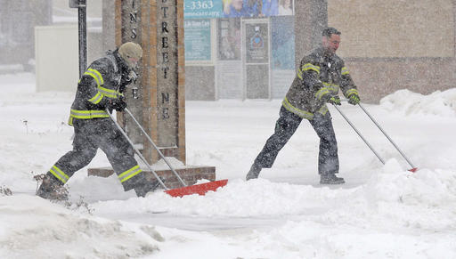 Firefighters Shane Weltikol, left, and Chad Nicklos clear snow in downtown Mandan, N.D., on Sunday.  The Bismarck Tribune/Tom Stromme