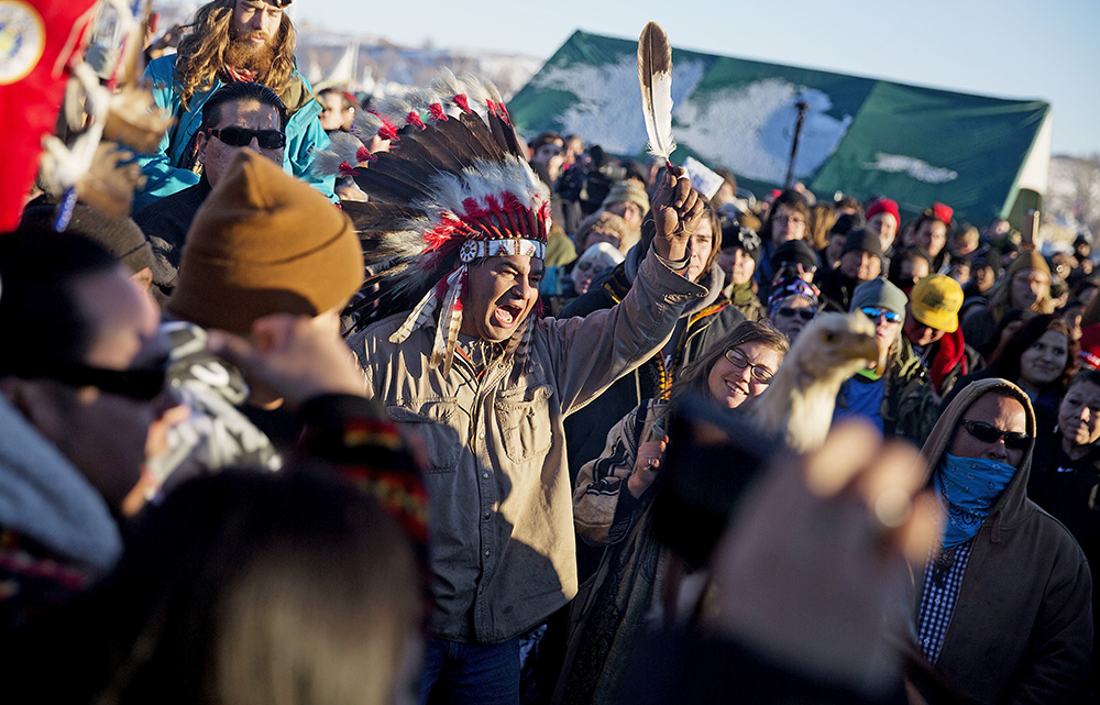 Protesters celebrate at the Oceti Sakowin camp after it was announced that the U.S. Army Corps of Engineers won't grant an easement for the Dakota Access oil pipeline in Cannon Ball, N.D., Sunday. <em>Associated Press/David Goldman</em>