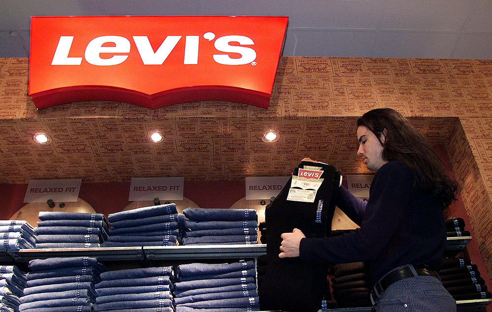 A store employee stocks a Levi's jeans display at a downtown Toronto department store. <em> Associated Press/CP Kevin Frayer</em>