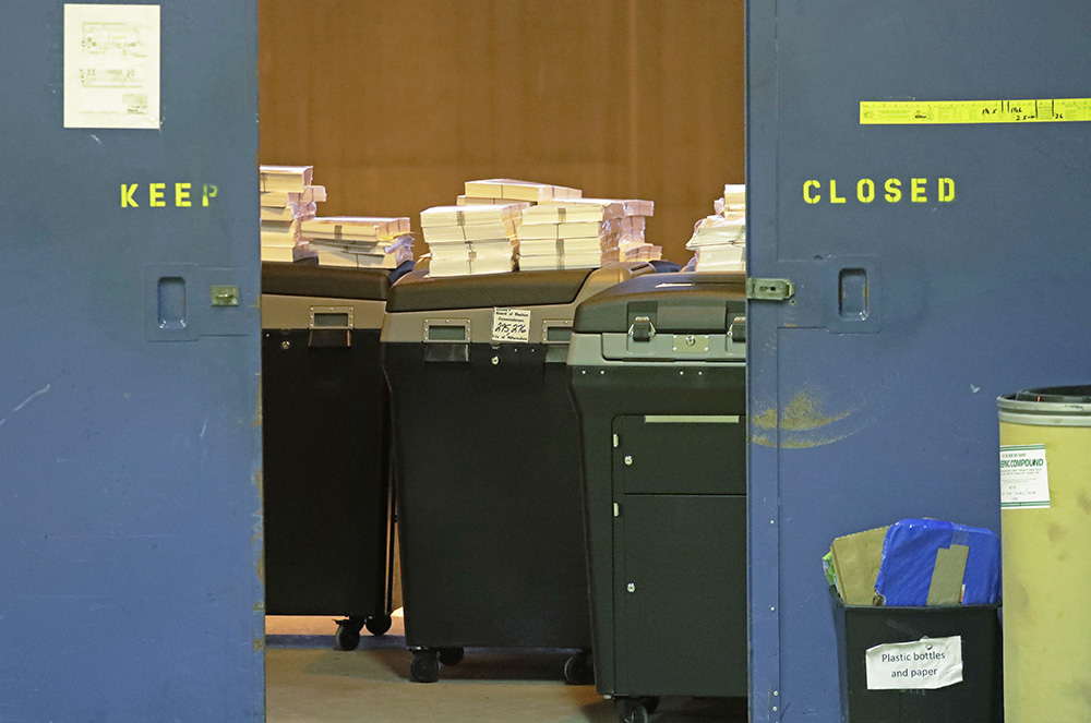Ballots are stacked up behind a door as a statewide presidential election recount begins Thursday in Milwaukee – the first candidate-driven statewide recount of a presidential election in 16 years. Donald Trump won the state by less than a percentage point over Hillary Clinton after polls long predicted a Clinton victory.  <em>Associated Press/Morry Gash</em>
