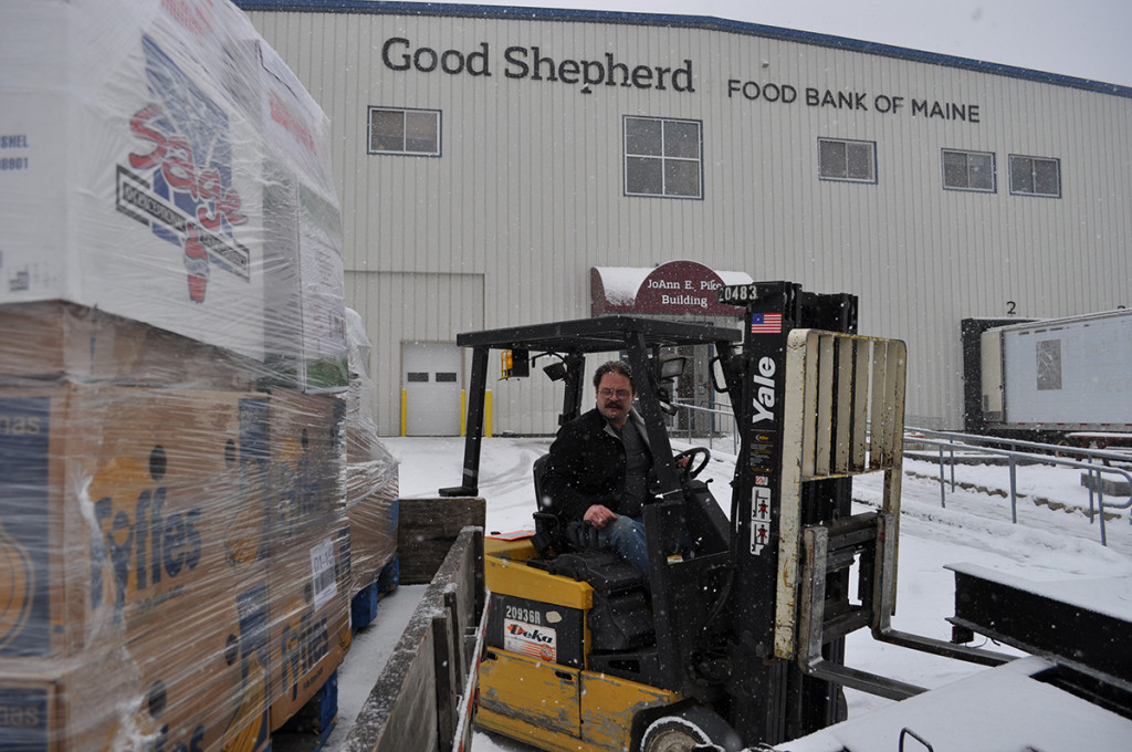 John Russell, a staffer at the Good Shepherd Food Bank warehouse in Auburn, moves foodstuffs. The facility is named for Good Shepherd founder JoAnn Pike, who started a food bank in her home in 1981.