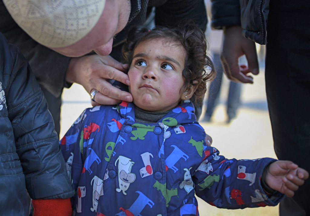 A Syrian child is comforted after she and other members of her family crossed into Turkey at the Cilvegozu border gate with Syria, near Hatay, southeastern Turkey, Sunday. <em>Associated Press/Emrah Gurel</em>
