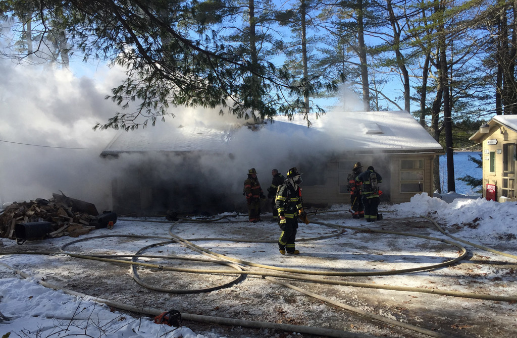 Firefighters work to extinguish a fire at 14 Golden Way in New Gloucester on Friday. The stubborn fire started under the home and spread through the walls.