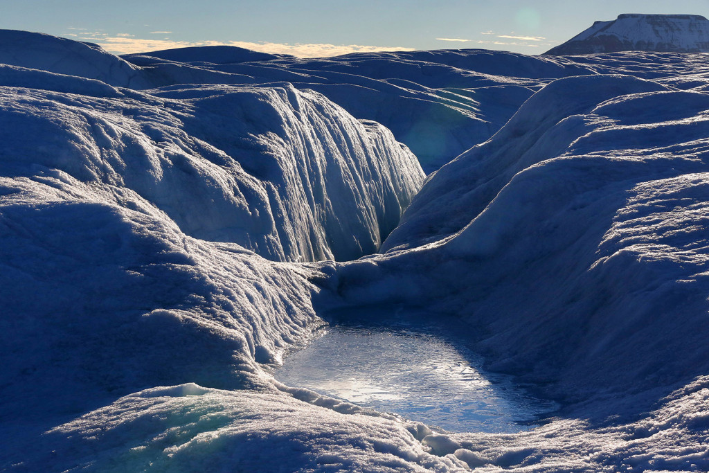 A pool of frozen water rests on the bumpy, often wet surface of Petermann Glacier.