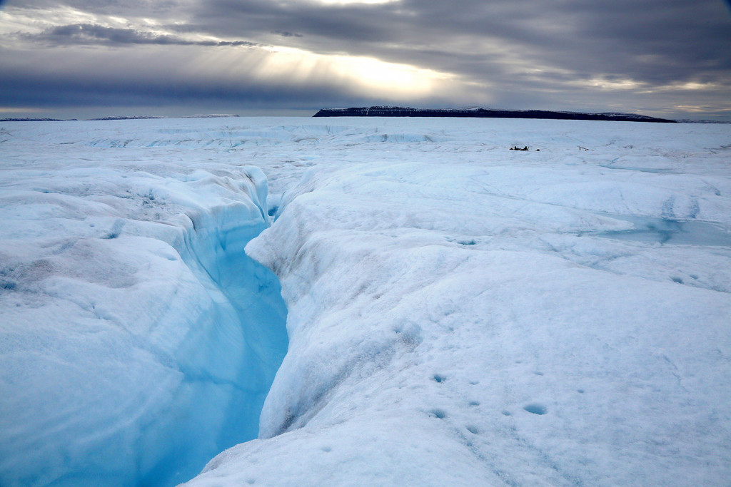 A deep gulley with rushing water feeds into a river on Petermann Ice Shelf. The shelf has reached a record small size after losing pieces larger than Manhattan in recent years.