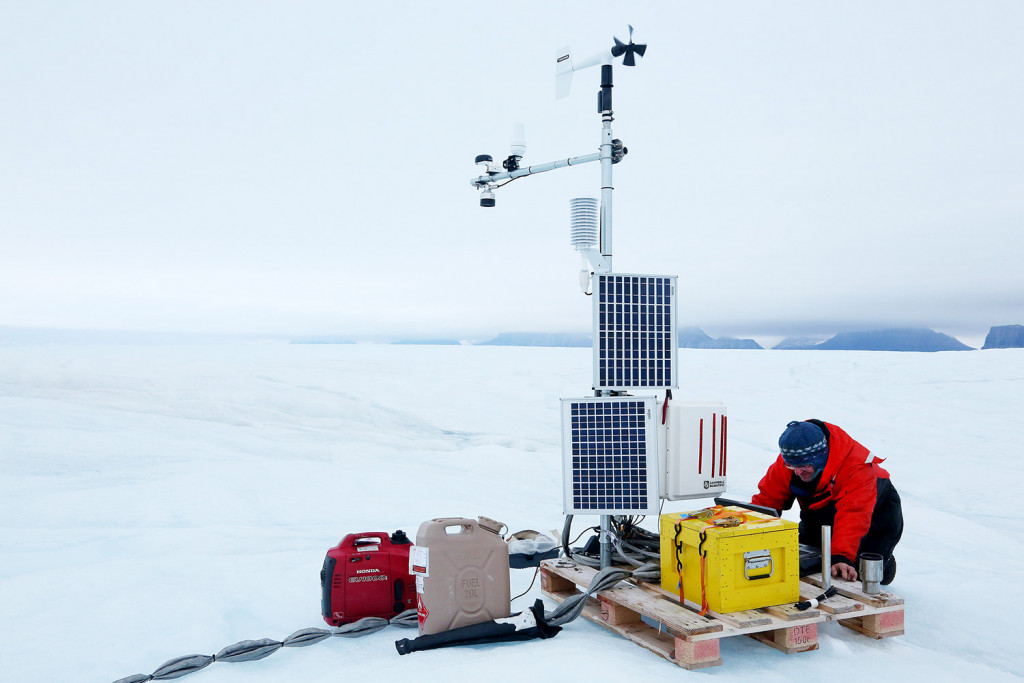 Andreas Muenchow finishes work on a weather station, which has a cable that runs deep into the ocean.