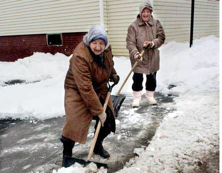 Marie Poulin, left, and her sister Rita shovel heavy slush in front of their home in Waterville on Sunday.  David Leaming/Morning Sentinel