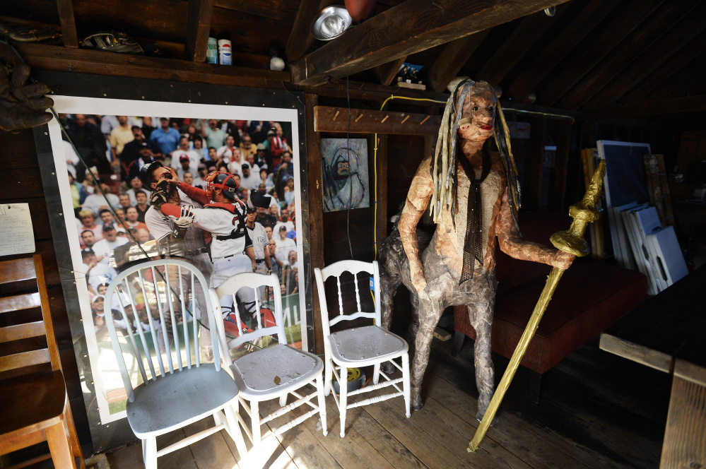 A centaur made by students at Noble High School stands watch beside sports memorabilia on display at Martin England's makeshift club.