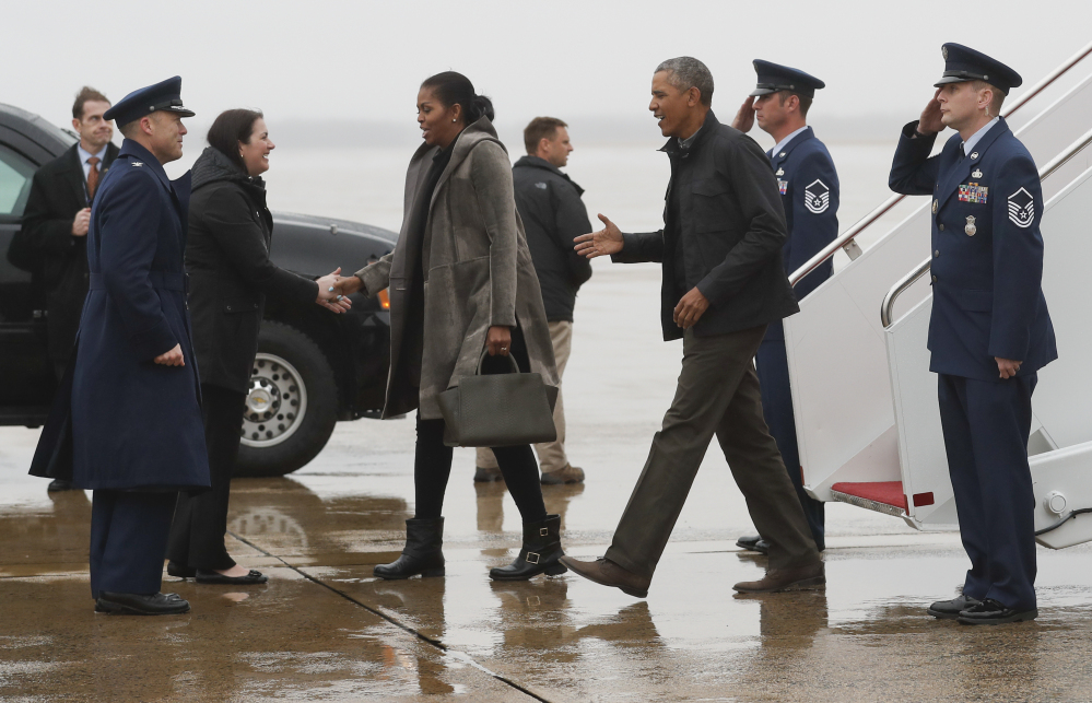 President Obama and first lady Michelle Obama are greeted Monday as they disembark from Air Force One at Andrews Air Force Base in Maryland. They were en route to Washington as they returned from their annual vacation in Hawaii.
