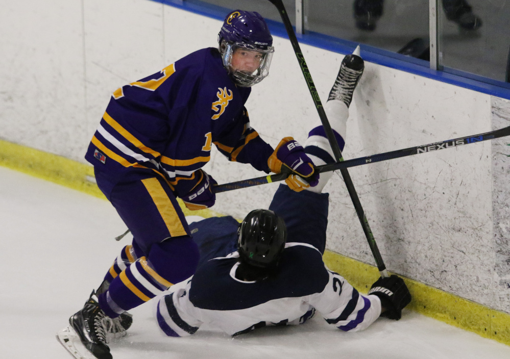 Cheverus' Jesse Pierce turns up ice after checking Portland/Deering's Joe Herboldsheimer during the first period Monday. Pierce scored in the third period to give the Stags a 4-2 lead.