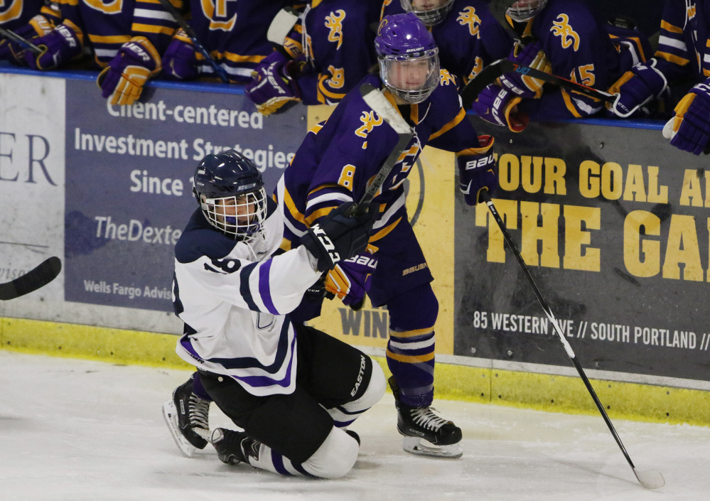 Portland/Deering's Cam Clifford, left, falls after colliding with Cheverus' Cam Dube during the second period of their game Monday. Dube had two assists for the Stags, who beat the Rams 5-2 to win the City Cup for the fourth straight year.
