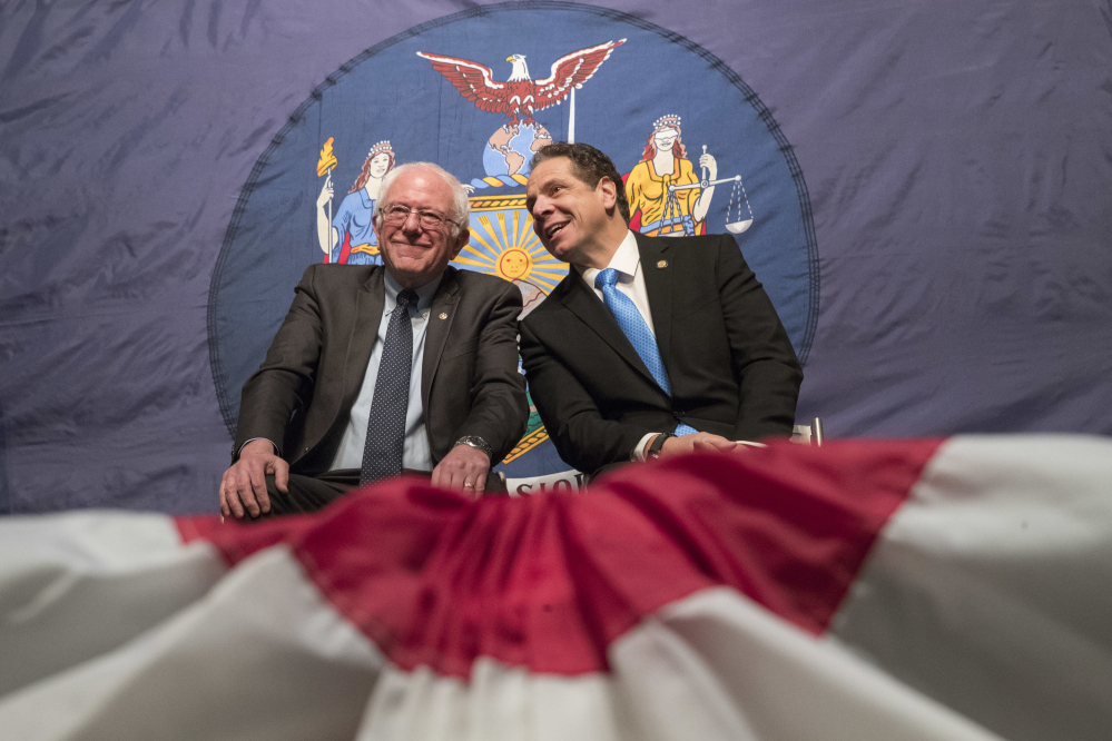 New York Gov. Andrew Cuomo, right, and Vermont Sen. Bernie Sanders appear onstage together during an event at LaGuardia Community College in New York. Under the Cuomo's plan, which requires legislative approval, any college student accepted to a New York public university or two-year community college is eligible to attend for free, provided their family earns less than $125,000.