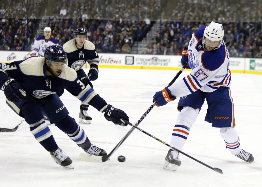 Edmonton's Benoit Pouliot, right, battles for the puck with Columbus defenseman Seth Jones in Tuesday's game at Columbus, Ohio. The Blue Jackets won their 16th straight, one shy of the NHL record.