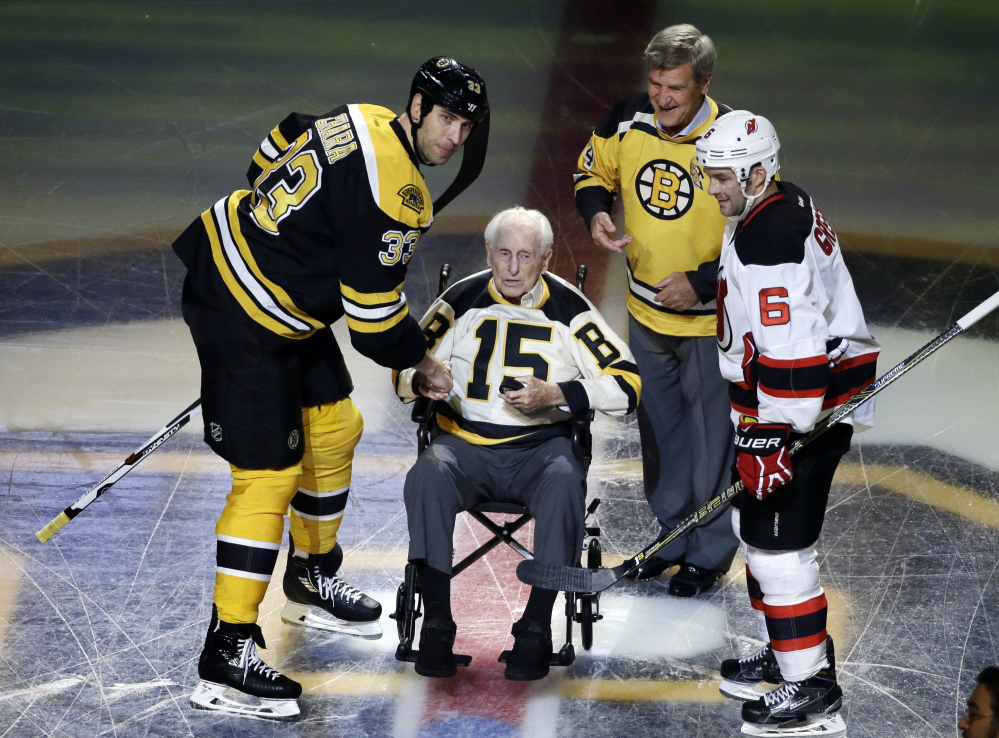 In this Oct. 20, 2016 photo, Boston Bruins defenseman Zdeno Chara , left, and New Jersey Devils defenseman Andy Greene join Bruins legends Milt Schmidt and Bobby Orr in a ceremonial puck drop before an game in Boston. Schmidt, a hockey hall of famer, died Wednesday at the age of 98, Bruins team spokesman Matt Chmura said Wednesday. He was the league's oldest living former player. Associated Press/Elise Amendola