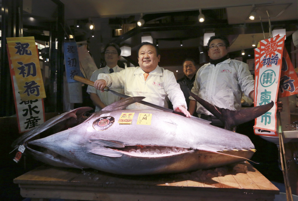 Kiyoshi Kimura, center, president of Kiyomura Co., poses with the 466-pound bluefin tuna he bought for $632,000 at the annual New Year auction, at his Sushi Zanmai restaurant near Tsukiji fish market in Tokyo on Thursday.