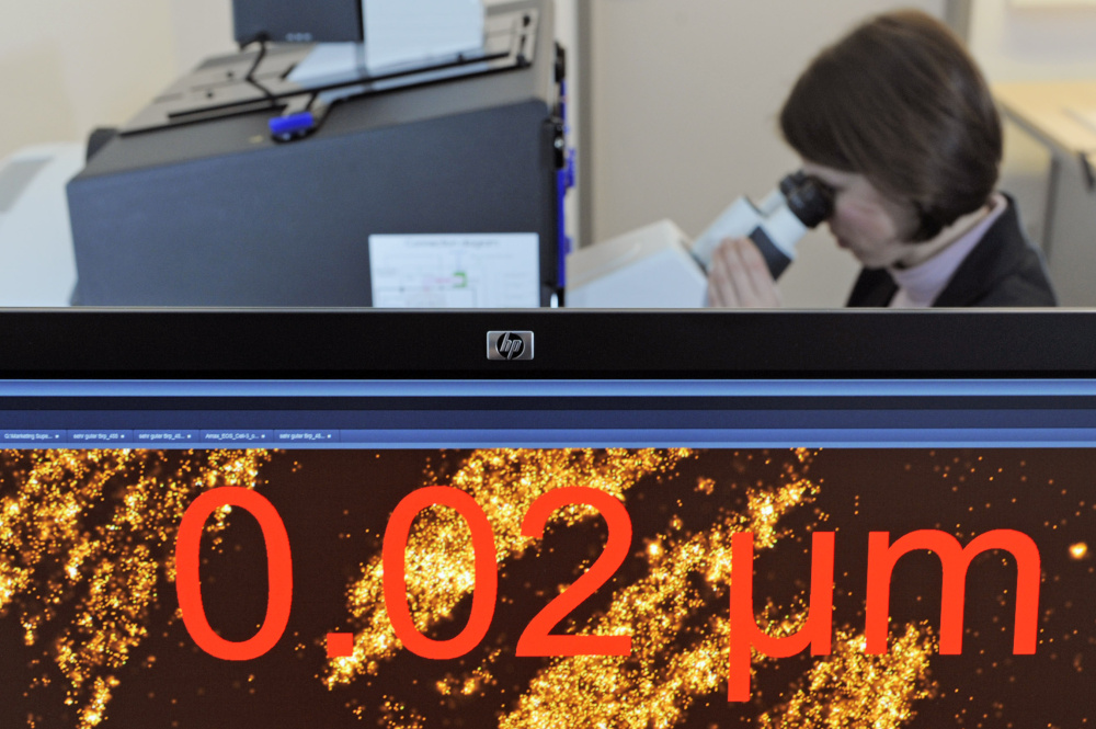 Almut Horch works with a microscope system behind a monitor where cancer cells are visualized in Jena, Germany.