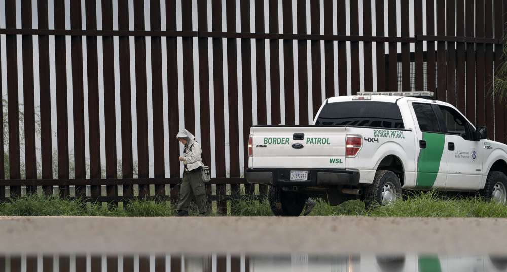 A U.S. Customs and Border Patrol agent passes birdwatcher Nancy Hill, 81, along a section of the border wall in November in Hidago, Texas.