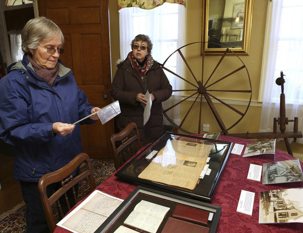 Ellington Historical Society Archivist Lynn Fahy, left, and Curator Nancy Long, right, look over Charles Price's diaries at the Nellie McKnight House in Ellington, Conn. Eight of the former town assessor's diaries were found and provide  first hand insight into history.