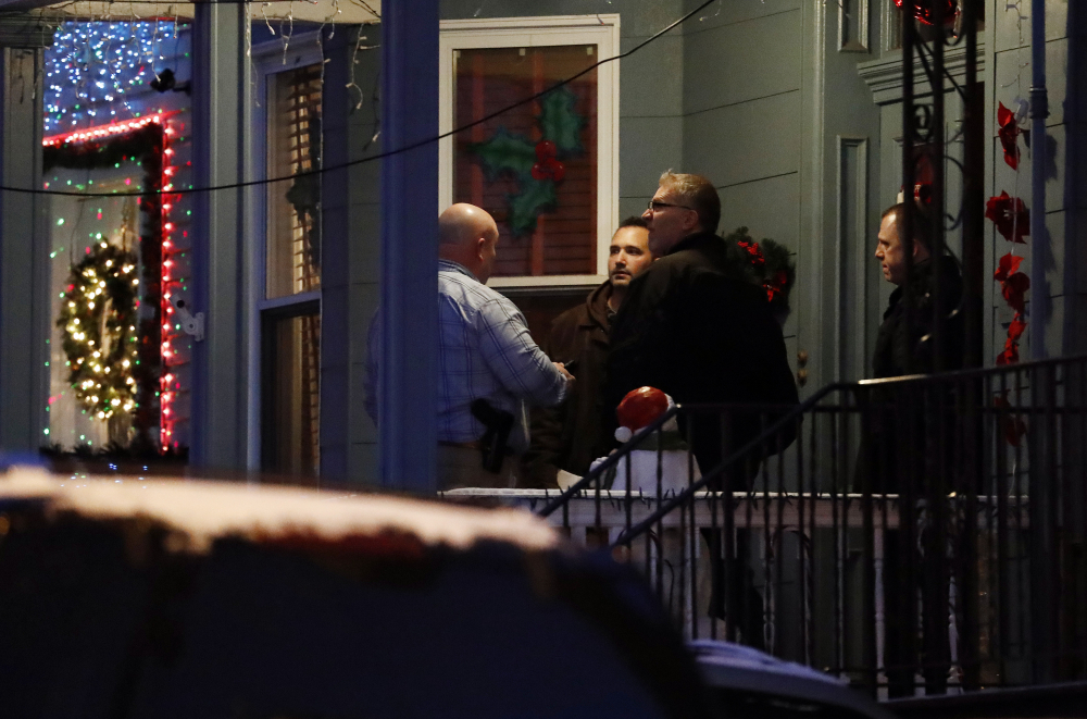 Officials are seen speaking to people believed to be family members of Esteban Santiago at a home in Union City, N.J., on Friday. Santiago is suspected of being the gunman in the shooting at the Fort Lauderdale-Hollywood International Airport.