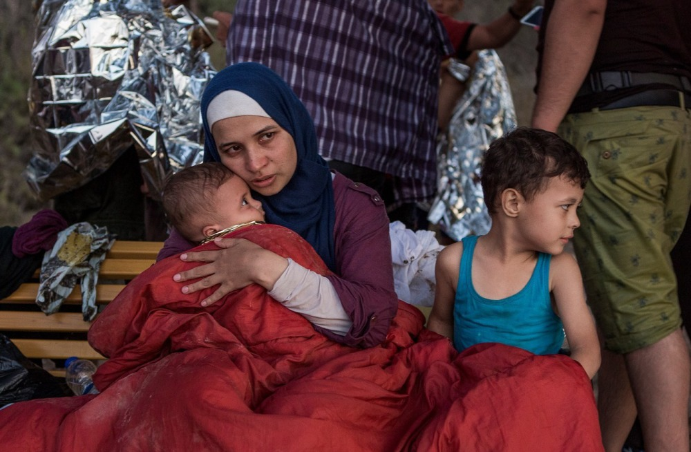 Syrian refugee Asmaa holds her 6-month old baby, Osman, while her 5-year-old, Abdul-Rahman, sits beside her in a camp in Greece. Asmaa and her husband, Omar, fled their home near Damascus last year.