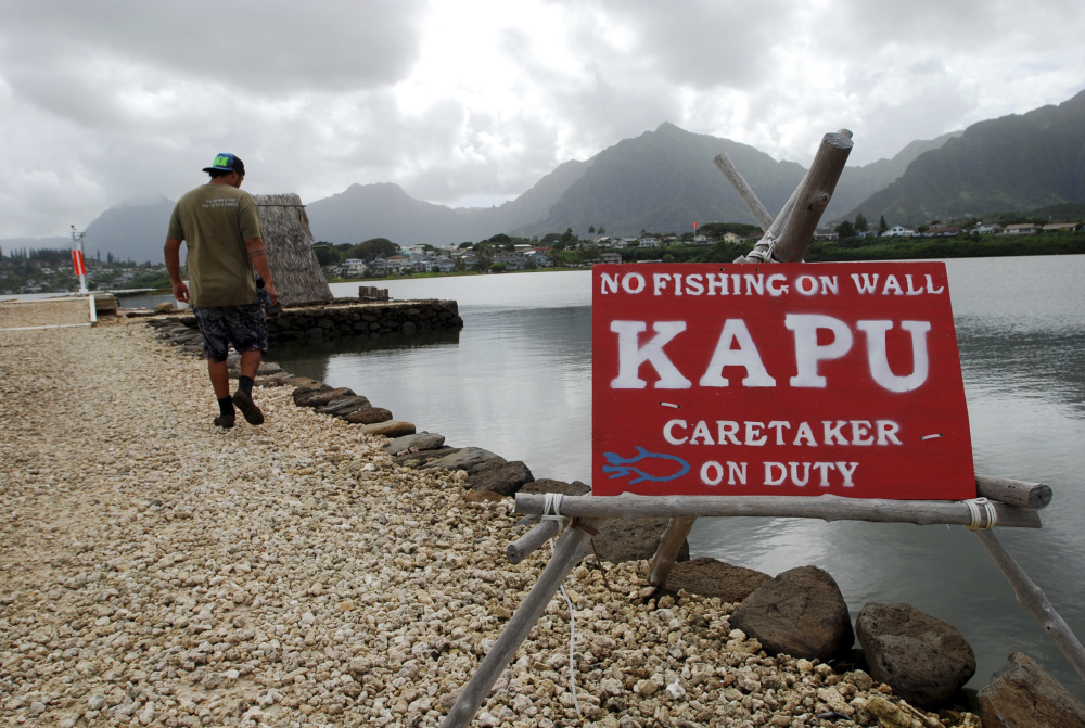 Conservation International's Luka Mossman, who restores and researches Native Hawaiian fishponds, walks along a barrier wall on Heeia fishpond in Kaneohe, Hawaii. U.S. officials are working on a plan to expand fish farming into federal waters around the Pacific Ocean.