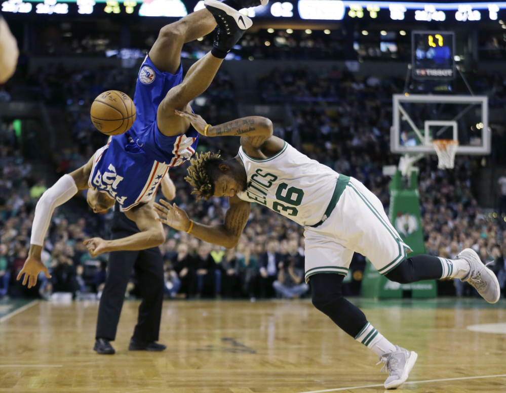 Philadelphia guard Gerald Henderson falls as he tries to block a shot by Boston's guard Marcus Smart in the second quarter Friday night in Boston.