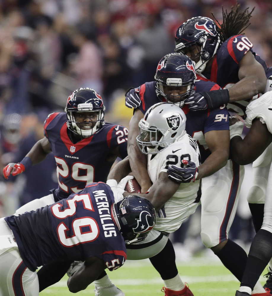 Oakland running back Latavius Murray (28) is hit by Houston's Whitney Mercilus (59) and Antonio Smith (94) during the second half Saturday game in Houston. Unless Miami beats Pittsburgh on Sunday, the Texans will play New England in the next round. (Associated Press/Eric Gay)