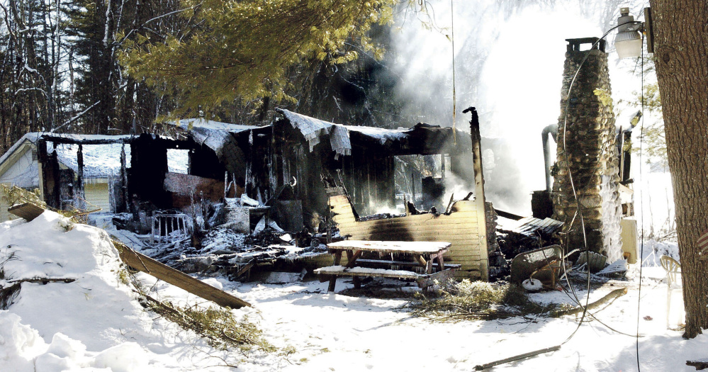 Smoke rises Sunday from the remains of a house on Washington Boulevard in China, where the owner, Randall Luck, was found dead Sunday morning outside the home.