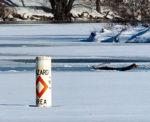 A hazard buoy marks the area near the outlet dam on Messalonskee Lake where a moving current reduces the thickness of the ice. Richard Dumont died Saturday after his snowmobile broke through the ice at the spot where a log, in background, was left.