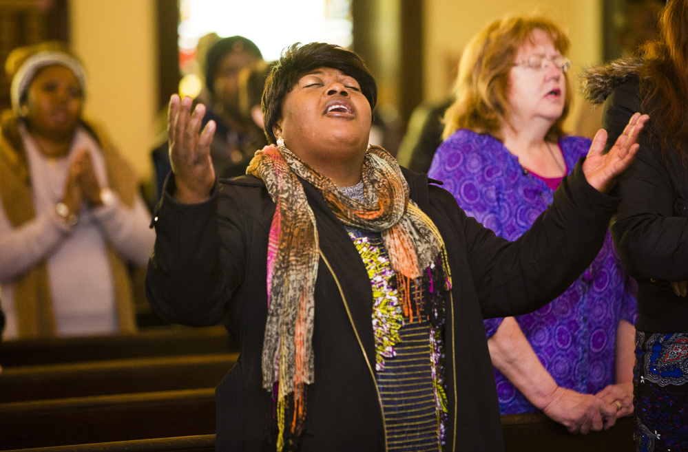 Esrher Kisimba, who came to the area five months ago from the Democratic Republic of the Congo, sings during Sunday service. Tim DiPaolo of Portland, an elder, deacon and usher at Deering Center Community Church, said immigrants have elevated the level of worship there.