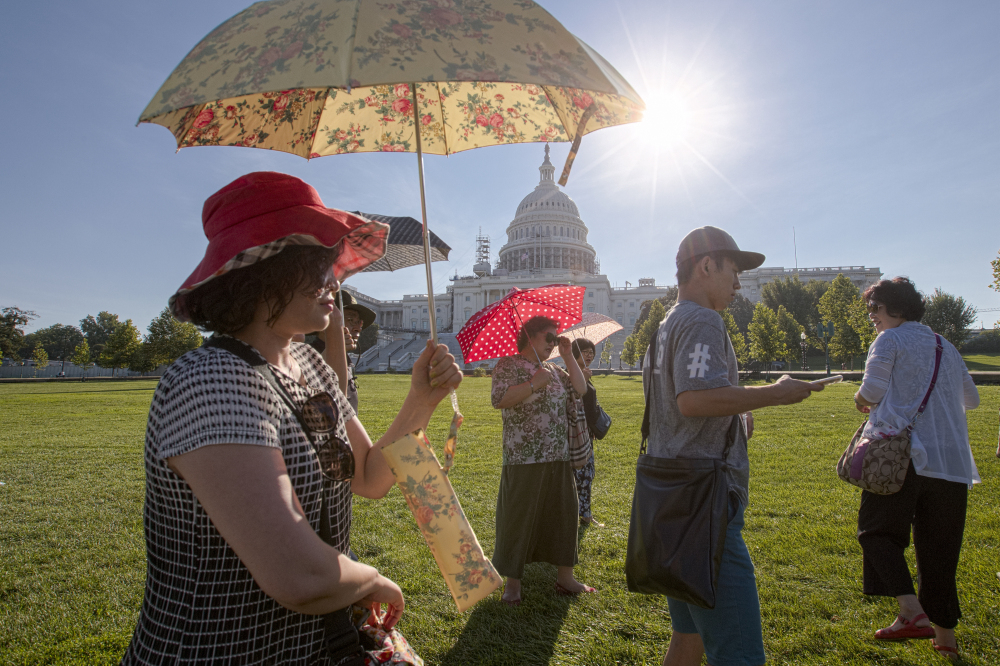 Visitors from Korea shield themselves from the early morning Augusta sun as they tour the Capitol in Washington, with temperatures lingering in upper 90s.