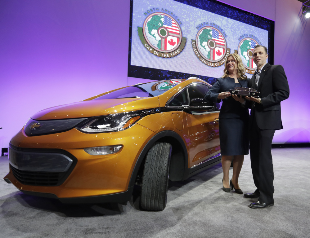 GM Executive Pam Fletcher and Chief Engineer Josh Tavel hold the trophy Monday after the Chevy Bolt, left, was named top car at the North American International Auto show.
