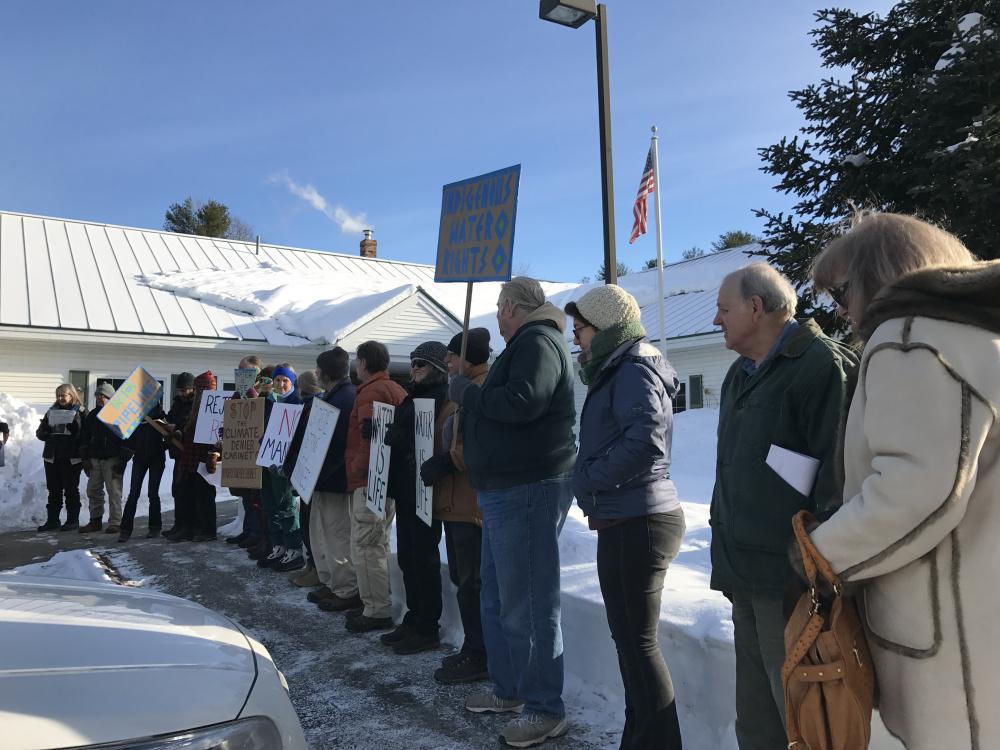 Protesters line up in the cold Monday before submitting a petition at the Augusta office of Sen. Angus King, asking him to reject President-elect Donald Trump's nominees.