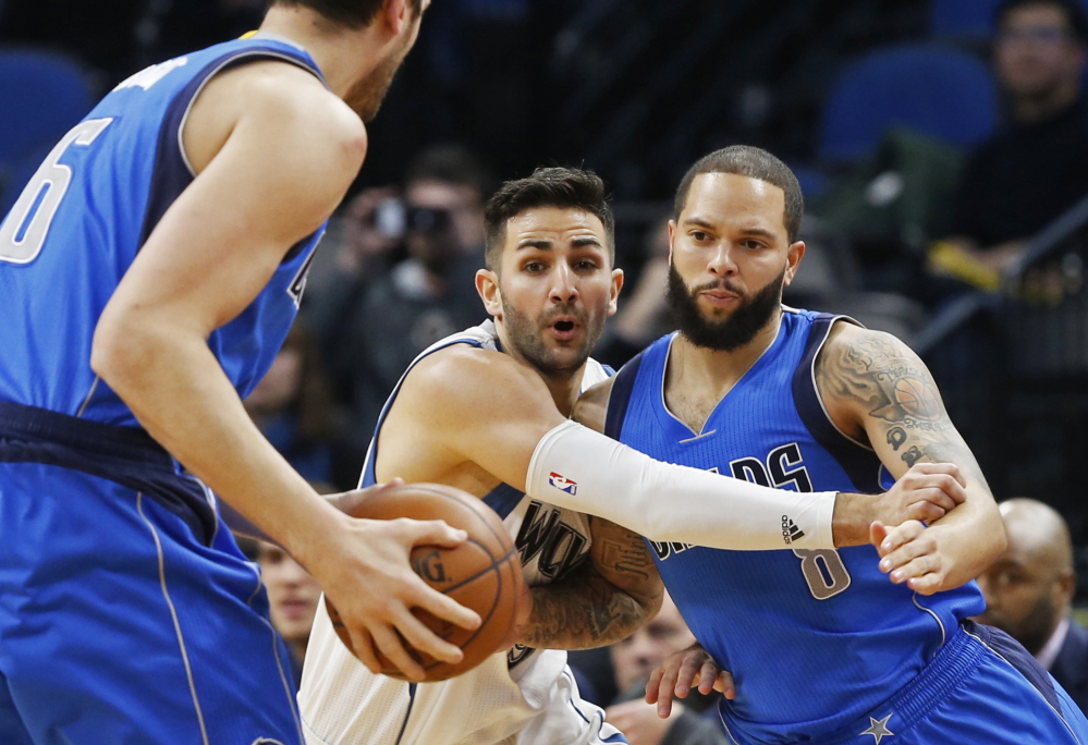 Minnesota's Ricky Rubio, center, defends Dallas' Deron Williams, right, during the Timberwolves 101-92 win Monday night in Minneapolis. Minnesota snapped a four-game losing streak with the win.