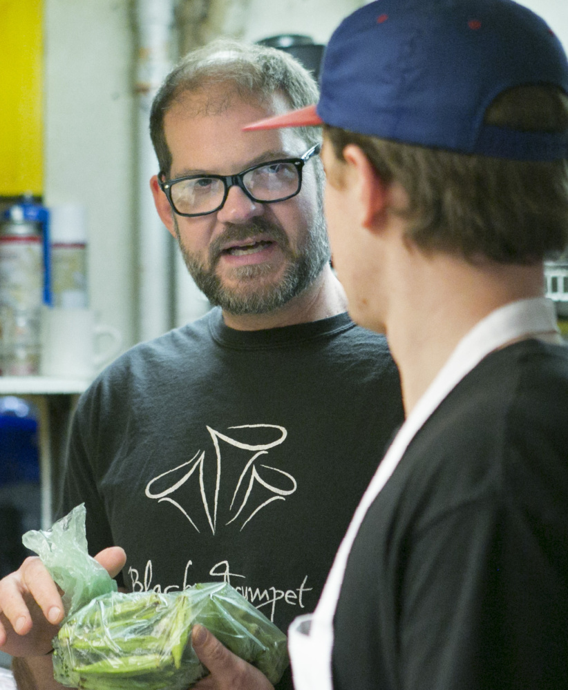 Evan Mallett talks with chef David Clegg in the kitchen at Black Trumpet in Portsmouth.