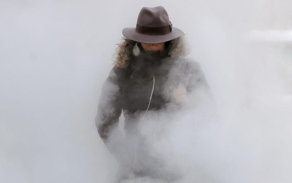 A woman walks through steam from an underground vent as temperatures dropped below minus 20 degrees Tuesday in Bucharest, Romania. In Albania, it snowed in the southern city of Saranda for the first time in 32 years.