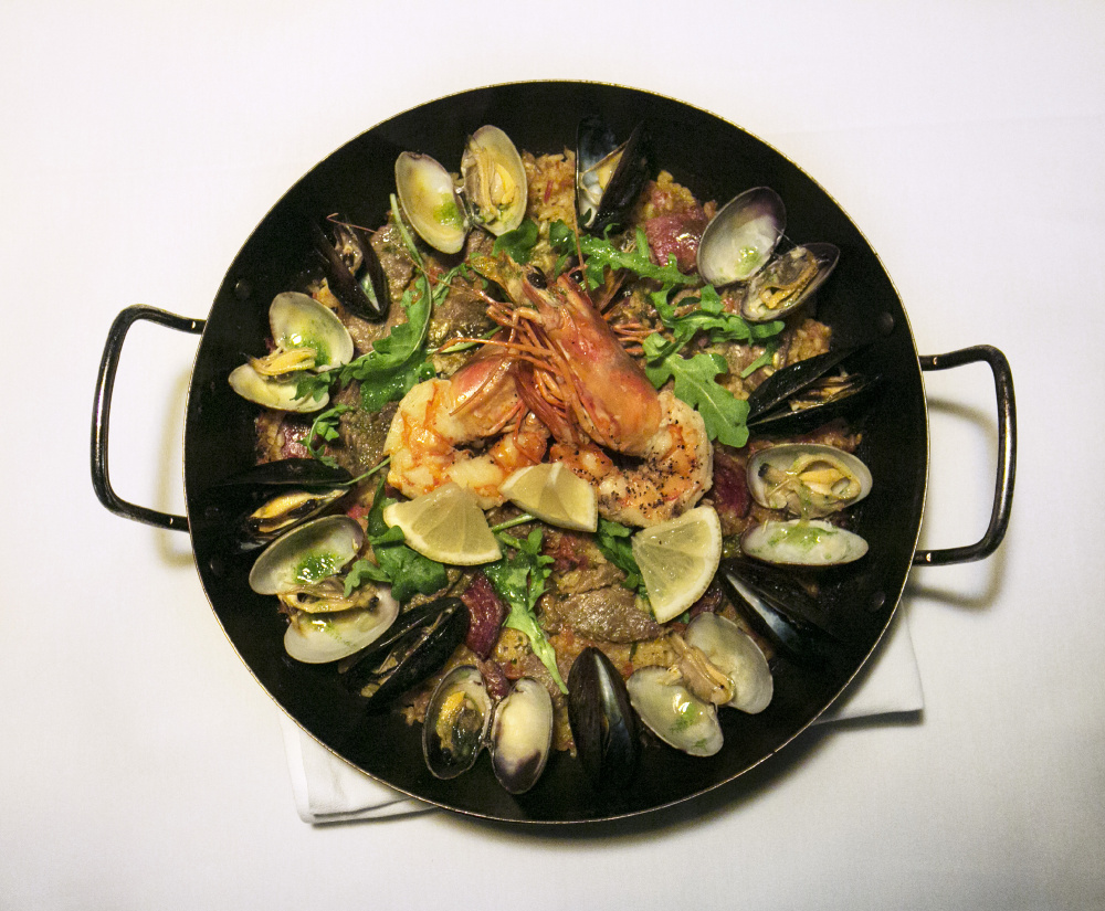 Paella de Mariscos made with calasparra rice, Spanish sofrito, chorizo, lobster, mussels, manilla clams, shrimp, arugula, garlic parsley oil and lemon wedges at Toroso in Kennebunk.