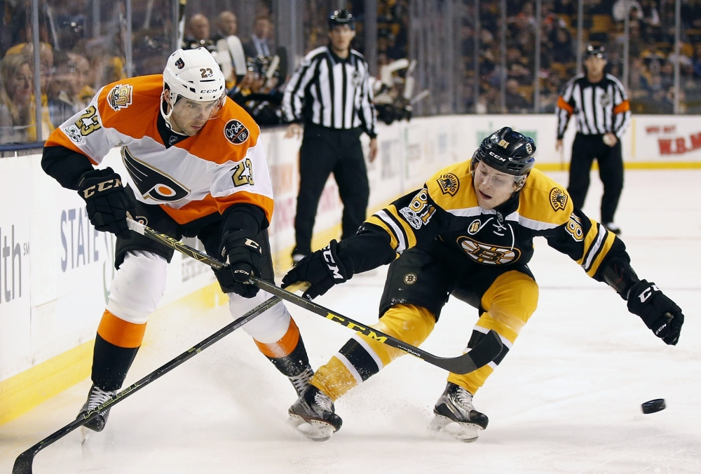 Philadelphia's Brandon Manning, left, tries to pass the puck as Boston's Anton Blidh pursues, during the first period of Saturday's game in Boston. (Associated Press/Michael Dwyer)