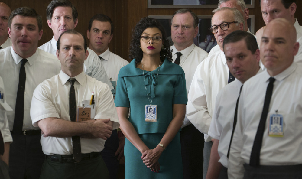 """Katherine Johnson, played by Taraji P. Henson, listens with her white male colleagues in a scene from """"Hidden Figures."""""""