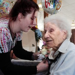 Hillary Dillingham pins a corsage on Ann Labin prior to her 100th birthday party at the Maple Crest Living Center in Madison on Monday.